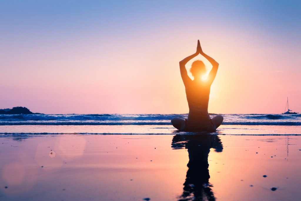 person meditating on beach at sunset