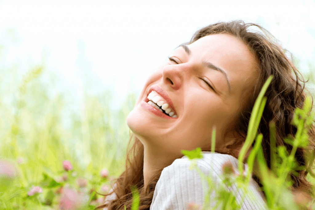 practice gratitude woman smiling in flowers