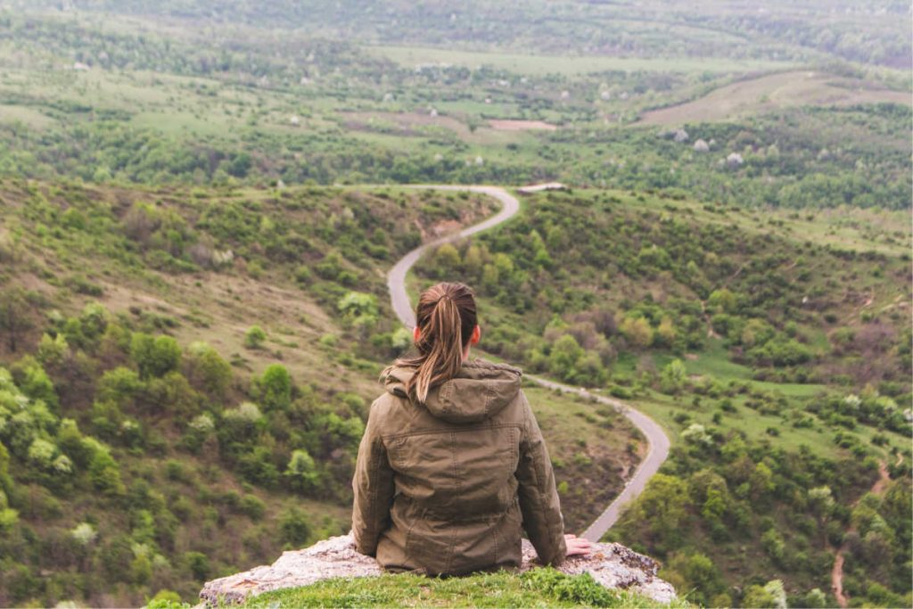 girl looking out from mountain - hero's journey