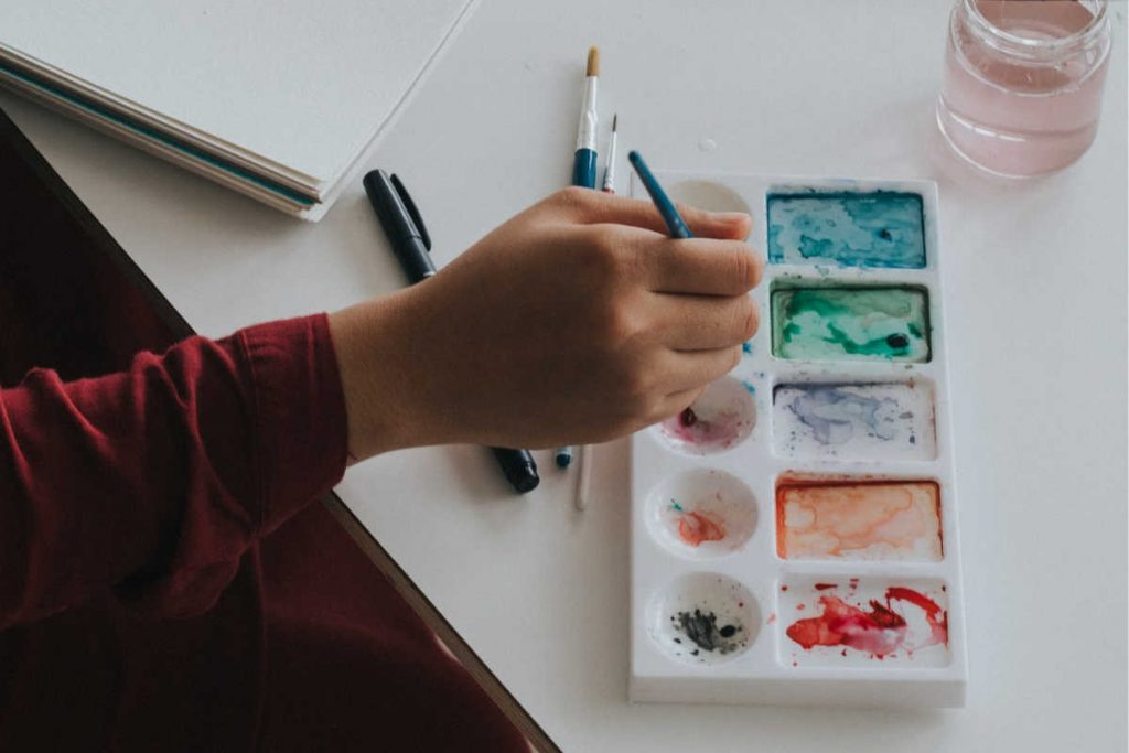 person painting with watercolors to recharge themselves creatively