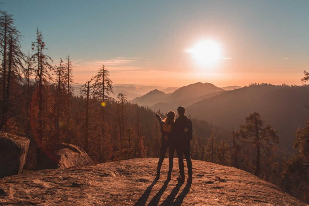 couple standing on mountain at sunset