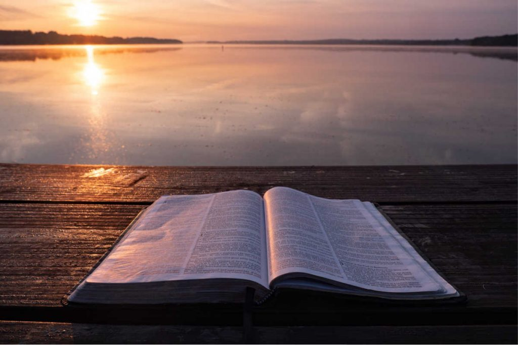 bible on outdoor table overlooking water at sunset