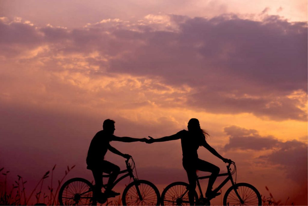 couple holding hands riding bike in sunset
