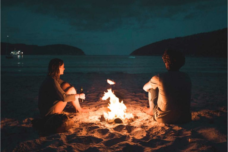 twin flame couple sitting by bonfire
