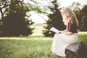 blonde woman sitting outside reading a book