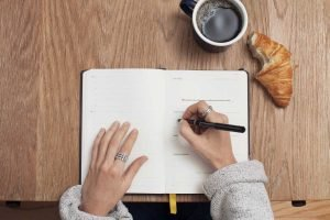 woman writing in notebook as part of manifesting ritual
