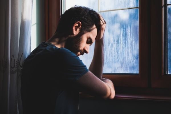 sad man looking out window