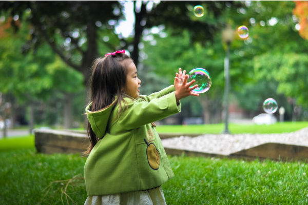 young female child with long dark hair trying to catch a bubble
