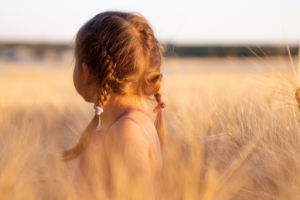 young girl standing in field