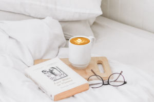 book, coffee and glasses on a white bed